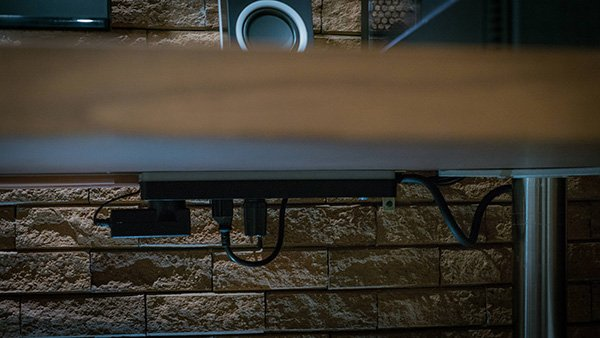 Surge protector mounted under desk.